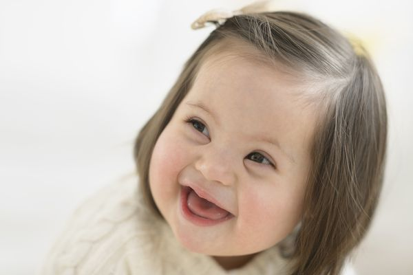 Hispanic toddler with Down syndrome laughing