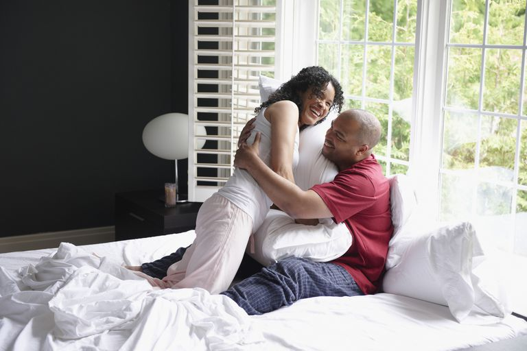 Happy couple playing in bed