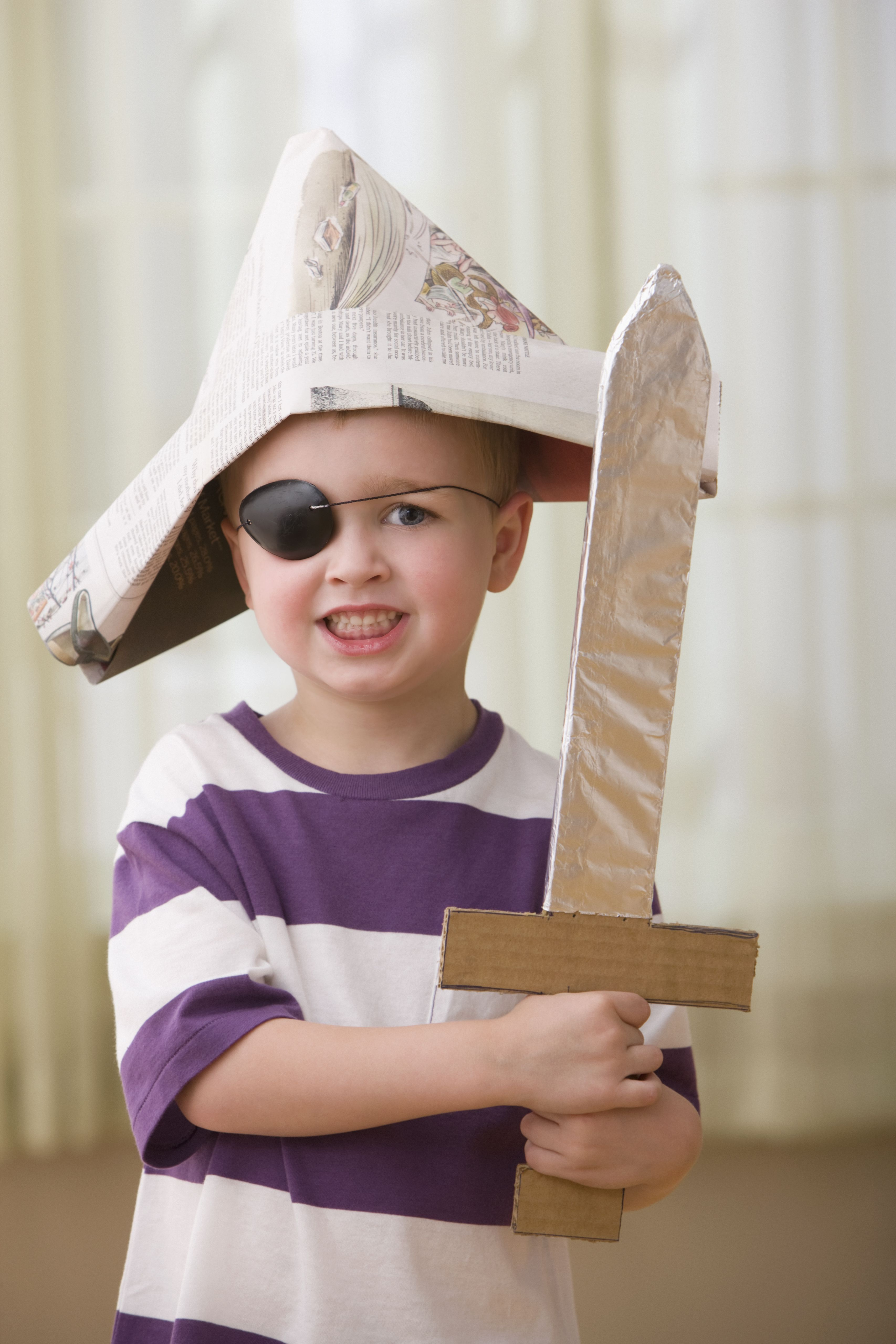 A boy wearing a paper pirate hat and holding a cardboard sword.