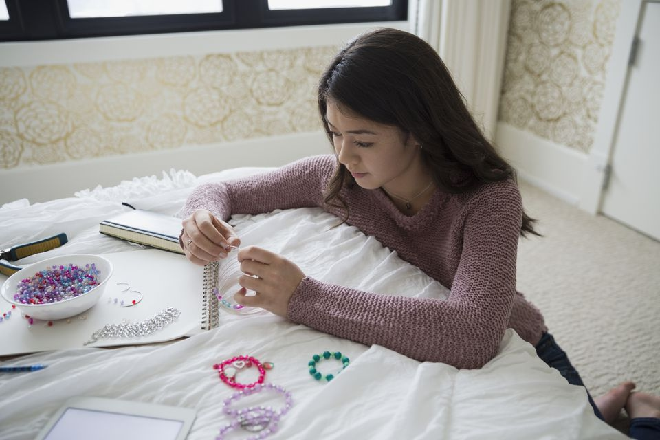 Teenage girl making jewelry on bed