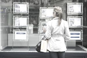 a woman looking at a display of available real estate