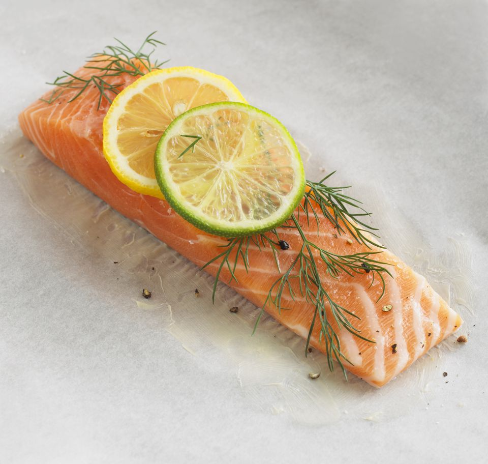 Salmon fillet garnished with dill, lime and lemon slices on baking parchment