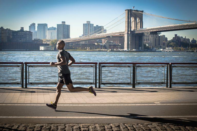 Mature man running along waterfront, New York, USA