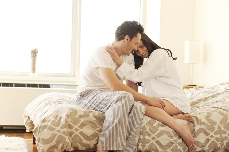 Couple sitting on bed cuddling