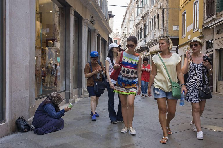 Shoppers walk through a retail district, passing by a woman begging for money on the street, symbolizing the ethical issues that plague consumer society.