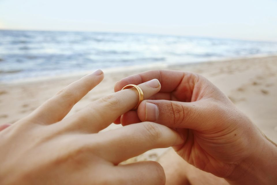 close-up of man putting wedding band on wife's finger