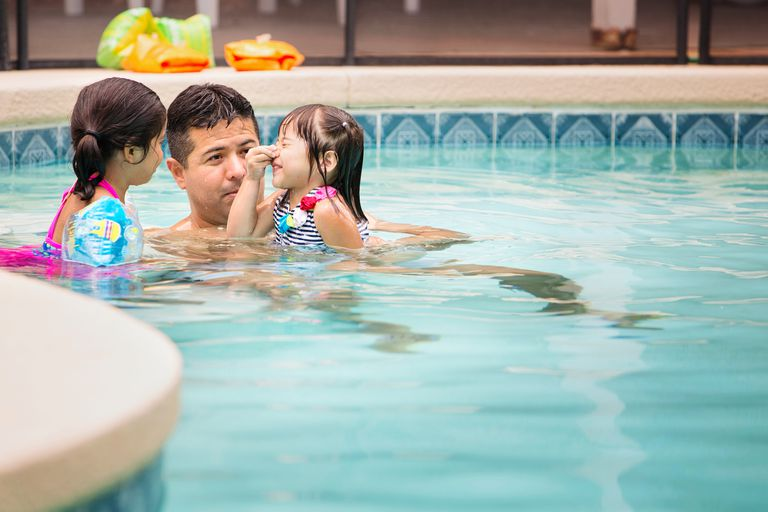 Father Teaching Swimming Lesson to Daughters
