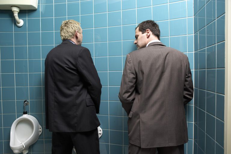 Two businessmen at urinals, one looking over other's shoulder