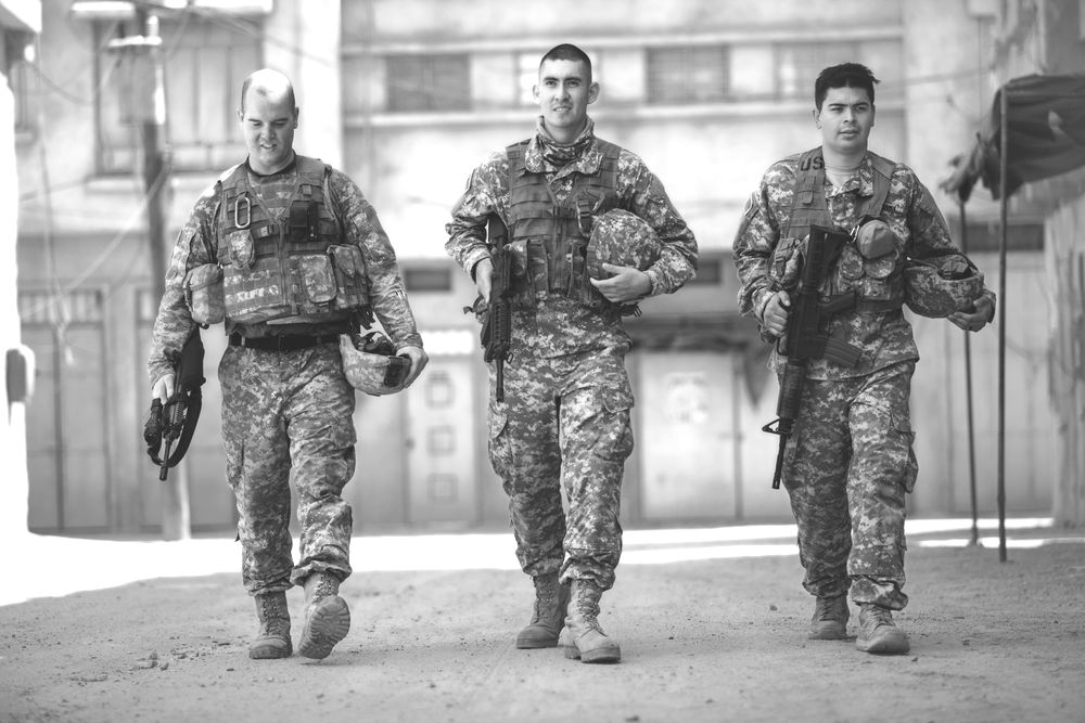 Army troops walk down a street in combat.