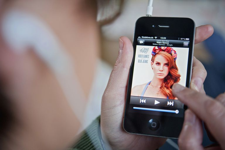 A closeup of an iPhone playing music with the earbud-wearing user in photo bokeh