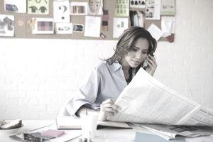 Businesswoman sitting behind desk reading newspaper