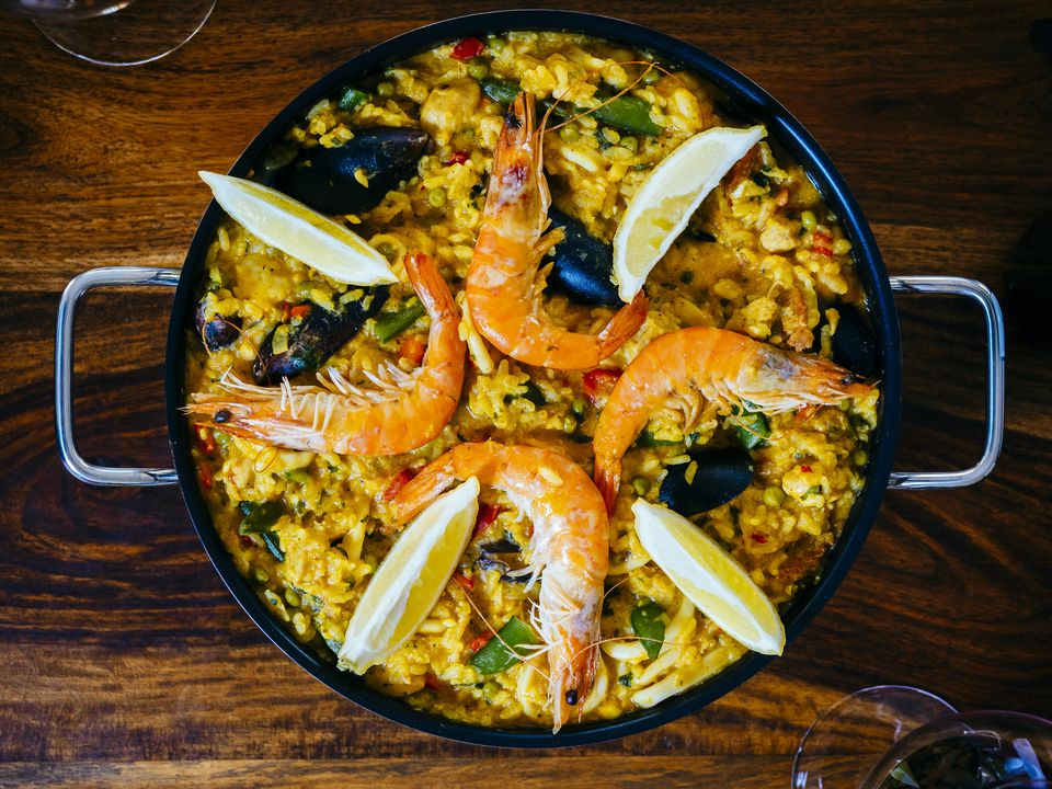 Fresh paella in pan on wooden table