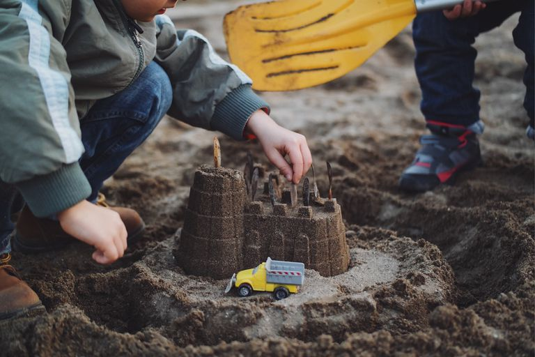 Low Section Of Boy Making Sand Castle By Brother At Beach