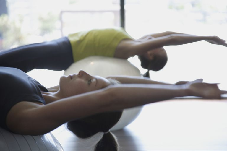 Two woman practicing Pilates on balls