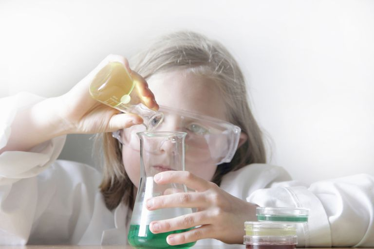 Girl pouring liquid into beakers