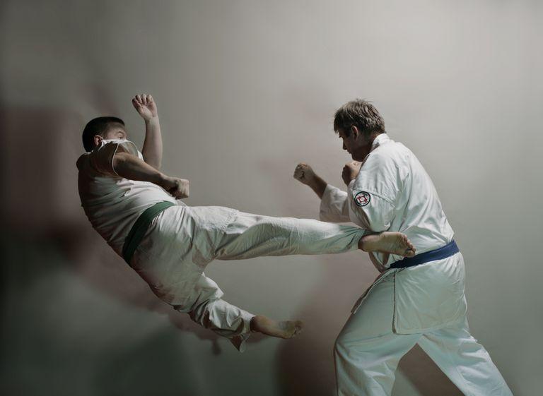 2 men practicing karate kicks
