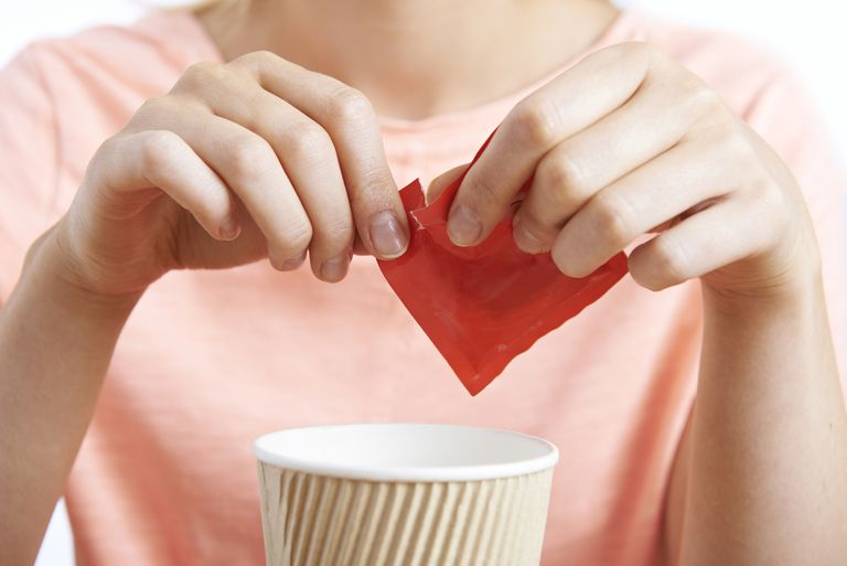 Woman opening package of artificial sweetener to put in her coffee