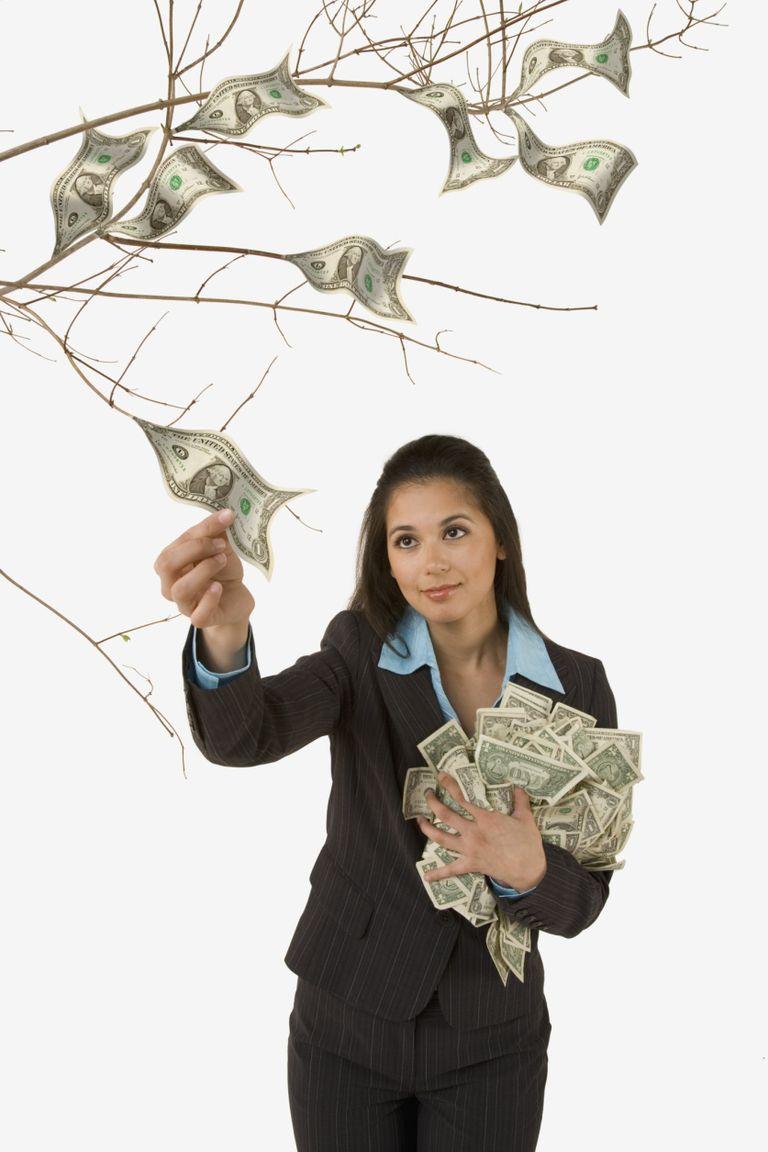Mujer recogiendo dinero de un árbol