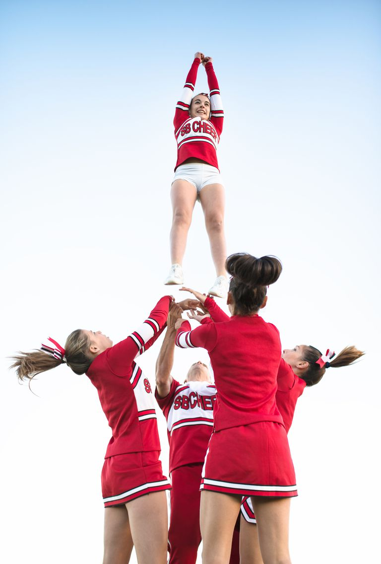 Cheerleaders throw up a girl in the air