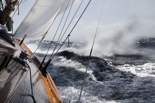 Yacht leaning in rough sea.