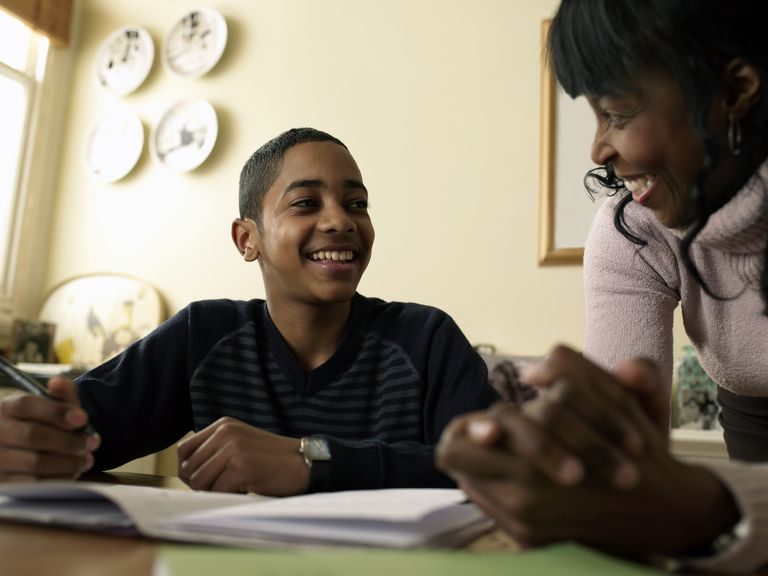 Boy (12-13) doing homework at kitchen table, mother assisting