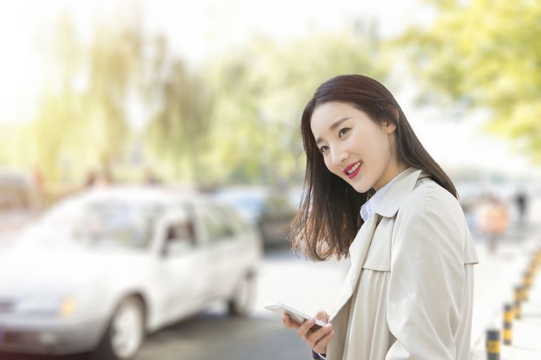 Woman waiting on the street using an app