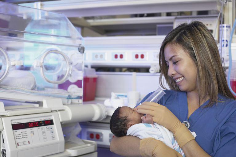 Female nurse feeding newborn African baby next to incubator