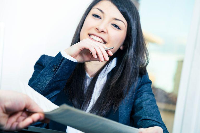 Woman handing resume to interviewer