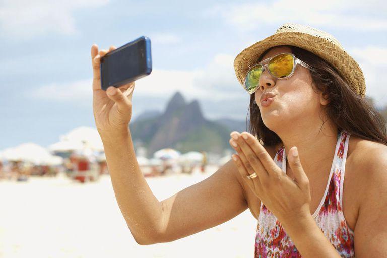 Mature woman taking a self portrait, Ipanema beach, Rio De Janeiro, Brazil