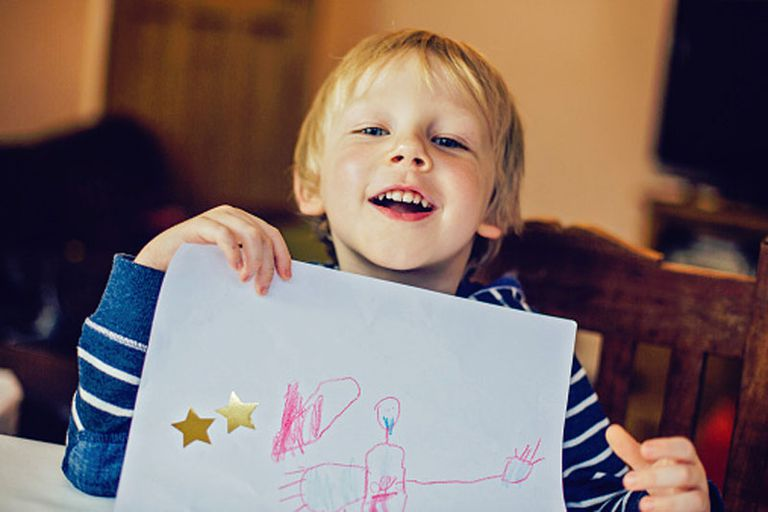 Young boy showing his drawing, smiling broadly