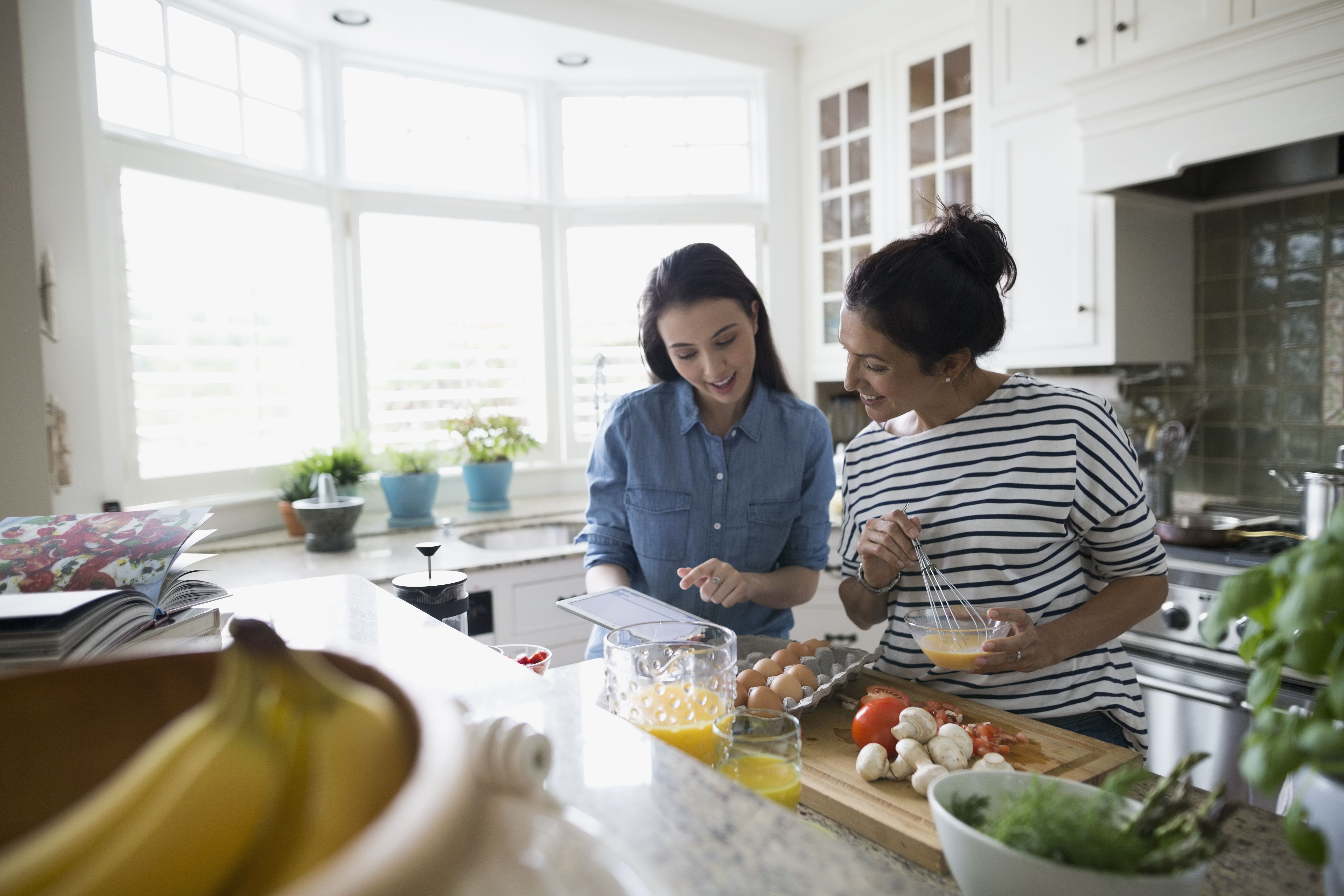 mother-and-daughter-cooking-with-recipe-in-kitchen-595347307-59dd5f72054ad900102dfac0.jpg