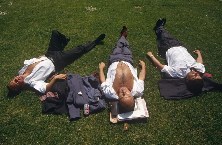 England - London - Three city office workers sunbathe during hot lunchtime