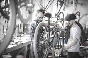 customer with mechanic looking at bicycle in work shop