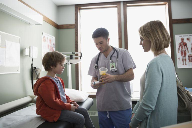 Male nurse explaining inhaler to boy