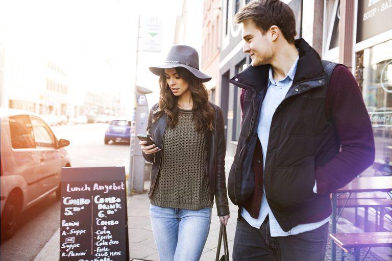 Germany, Berlin, young couple walking along sidewalk
