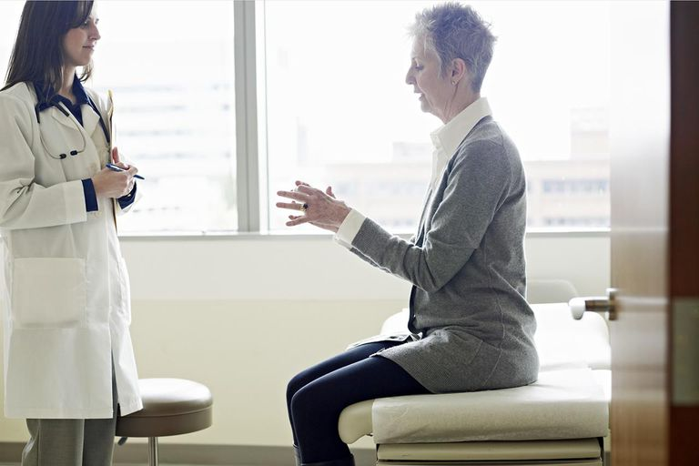 Female doctor in discussion with mature female patient in exam room