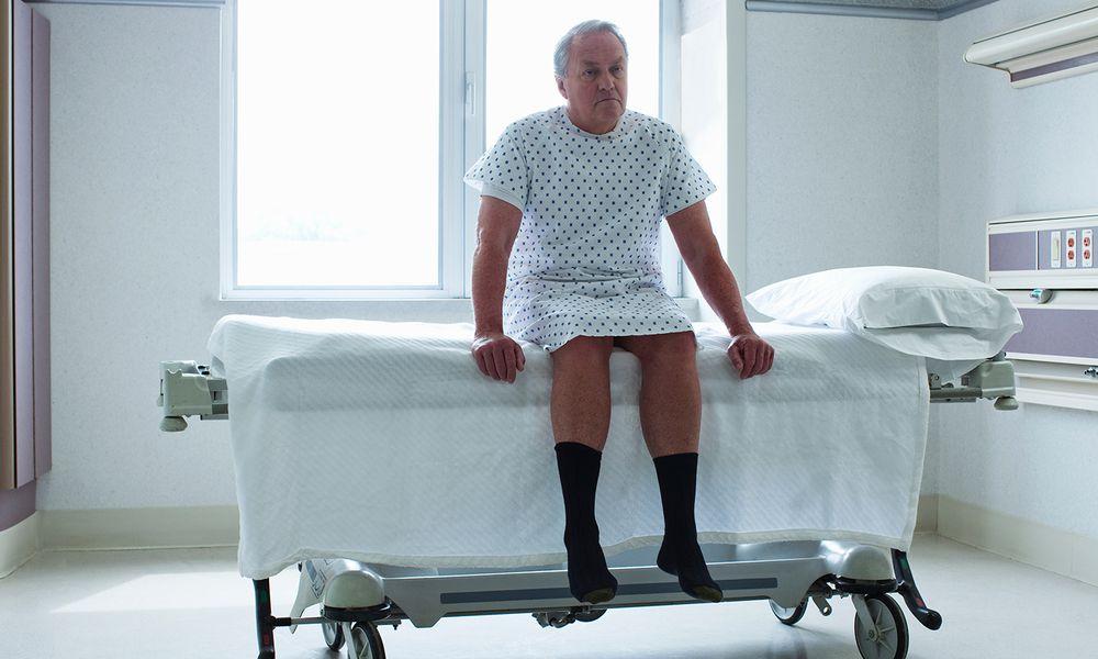 Senior man sitting on bed in hospital room