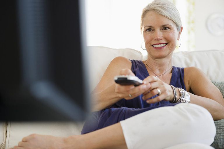 Senior woman watching television, smiling