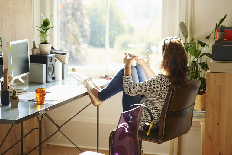 Pensive woman looking through window with feet up on desk in sunny home office