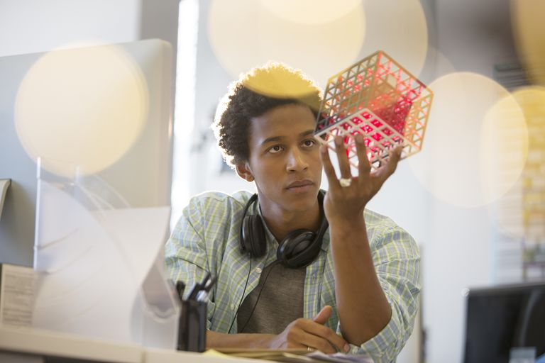 African American businessman examining cube at desk in office