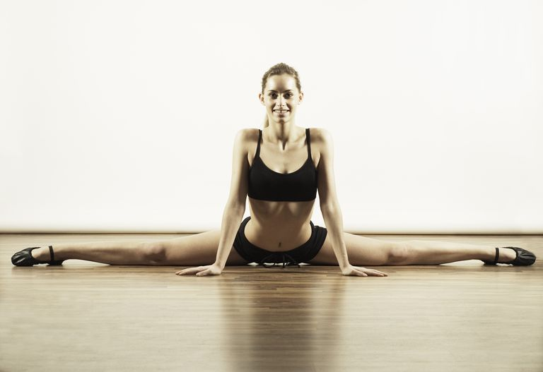Young woman in sportswear stretching against white background