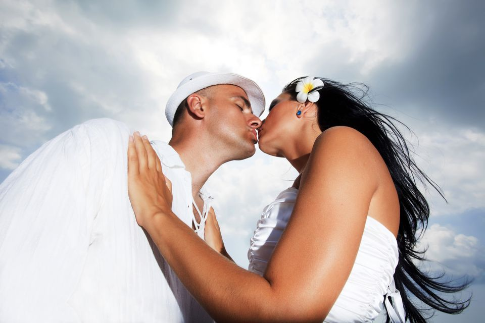 married couple kissing against the sky.