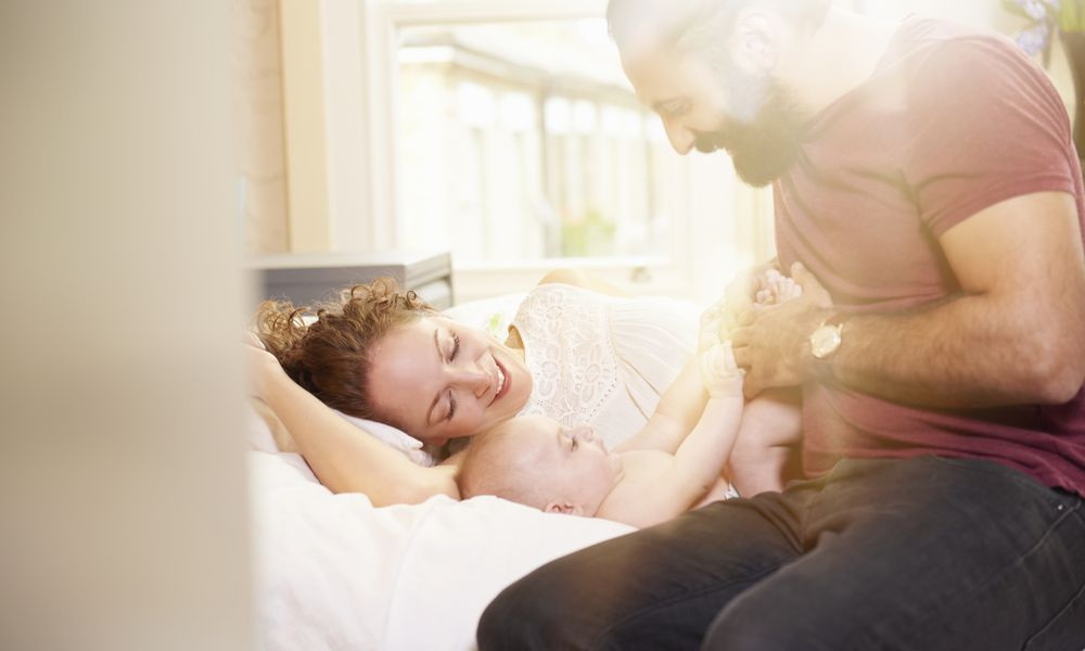 Parents playing with baby in bed at home, conceived after endometriosis infertility