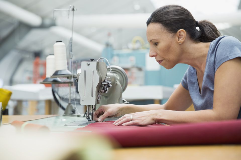 Worker using sewing machine in textile manufacturing plant
