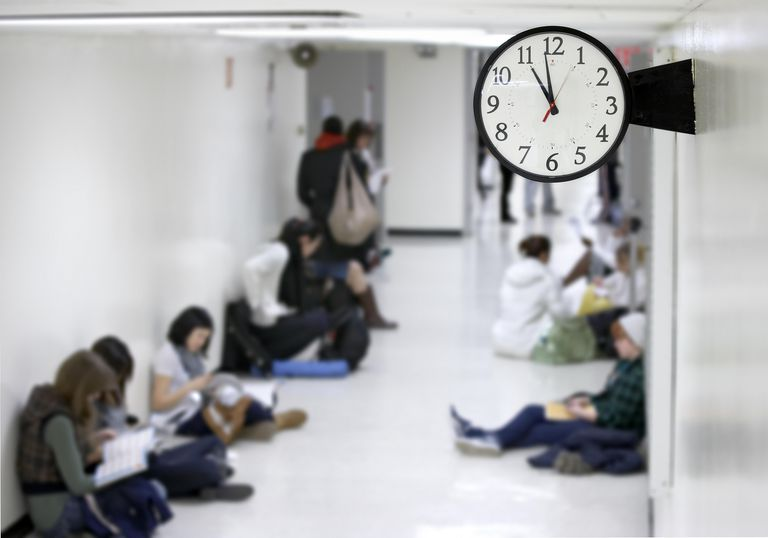 clock in school hallway with students sitting around