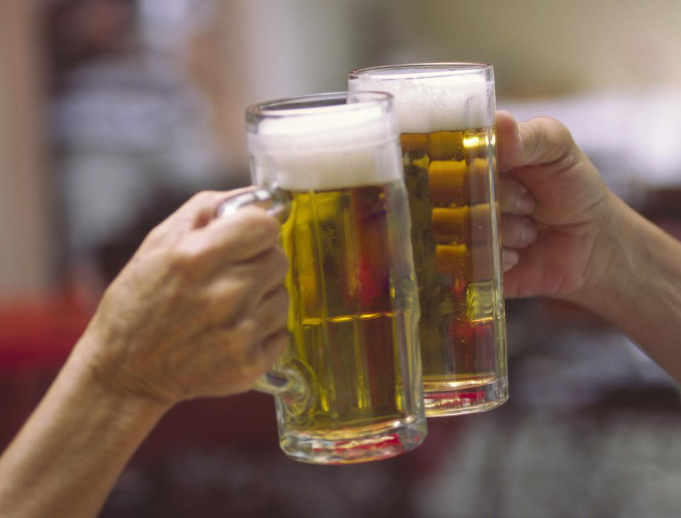 Mature couple toasting with beer steins, close-up of hands