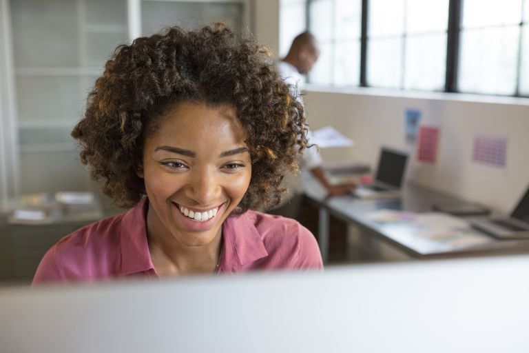 Beautiful black woman smiles at how much she has been able to improve her productivity and stress level with these tips.