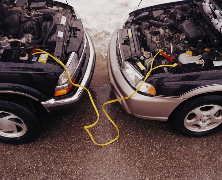 Two cars connected to jumper cables, elevated view