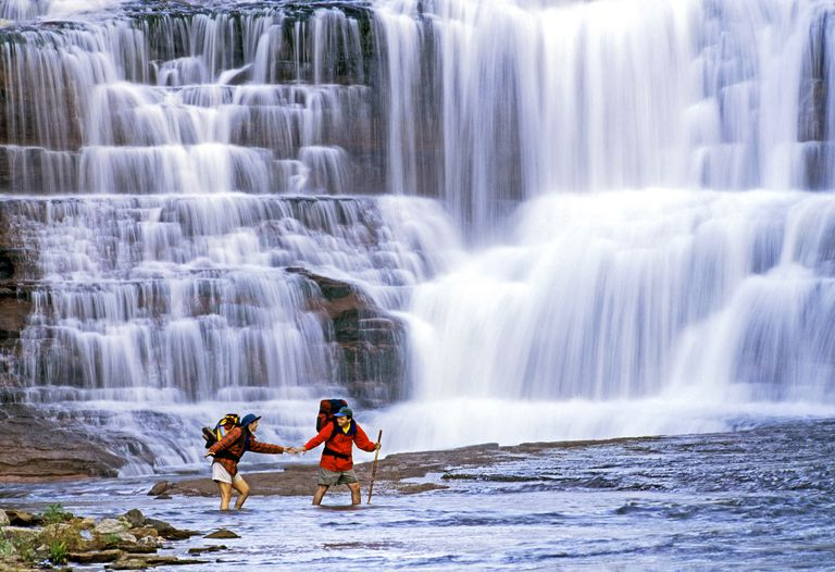 A couple wades a river below a waterfall.