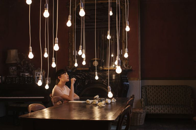Woman sitting at a table surrounded by hanging lightbulbs